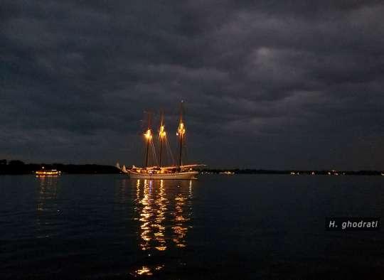 شبی ابری و قایقی با چراغهایش